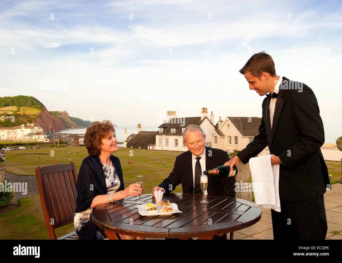 An older couple being served champagne outdoors  at a hotel on the south coast of Devon - Stock Image