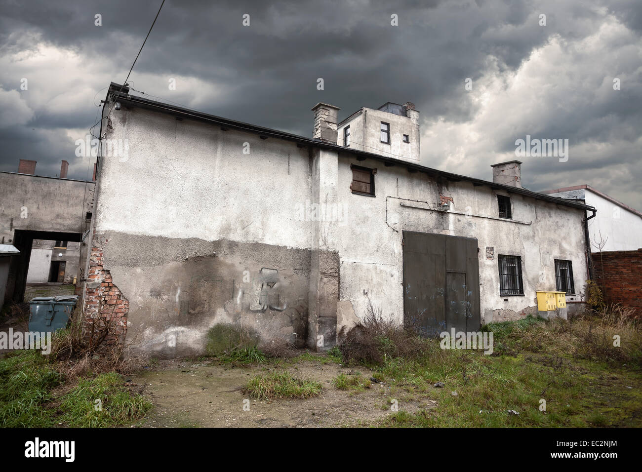 Sullen abandoned warehouse with stormy sky. - Stock Image