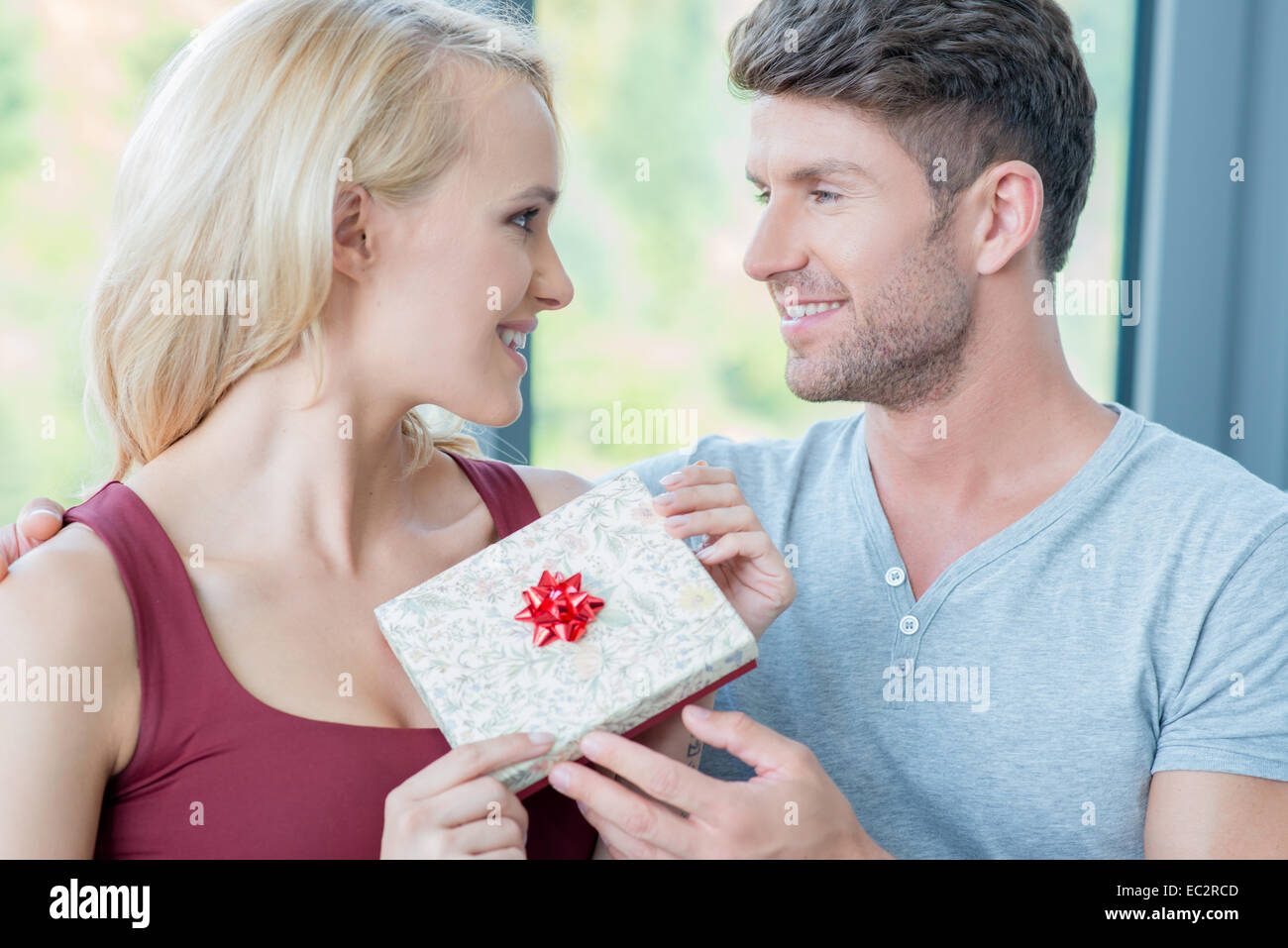 Loving man giving his wife a gift - Stock Image