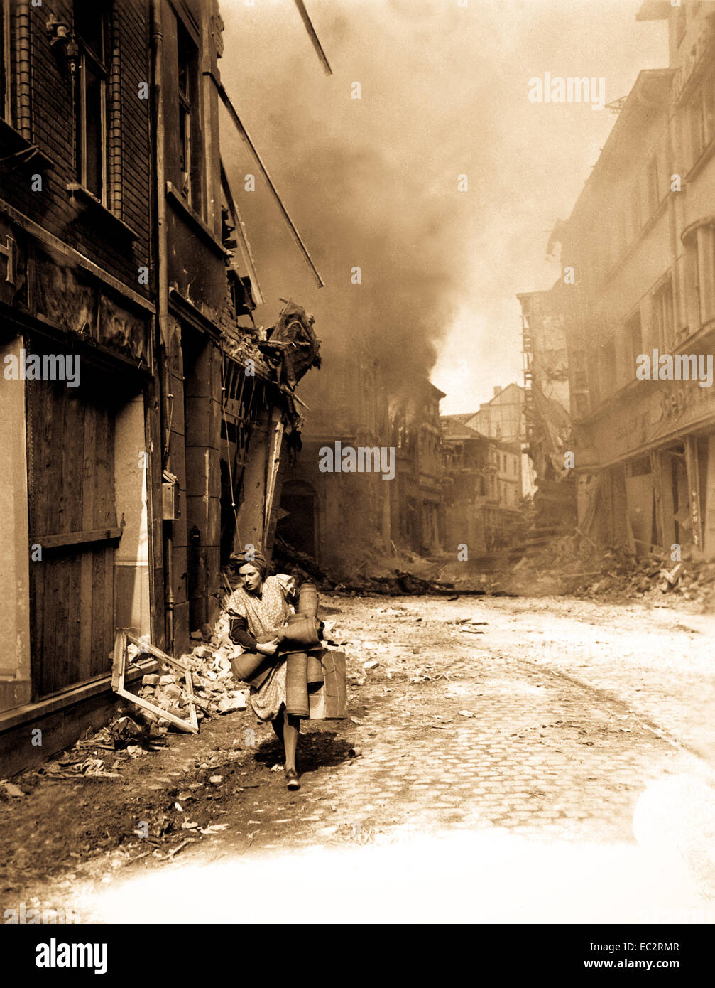 German woman carrying a few possessions runs from burning building in Seigburg, Germany.  Fire started by Nazi saboteur. - Stock Image