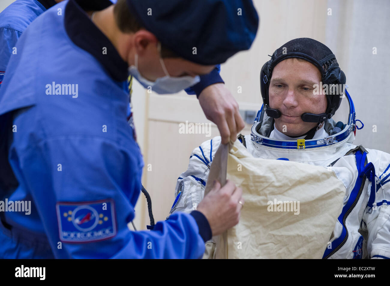 Expedition 42 Flight Engineer Terry Virts of NASA  is helped into his Russian Sokol suit as he and fellow crewmates, - Stock Image