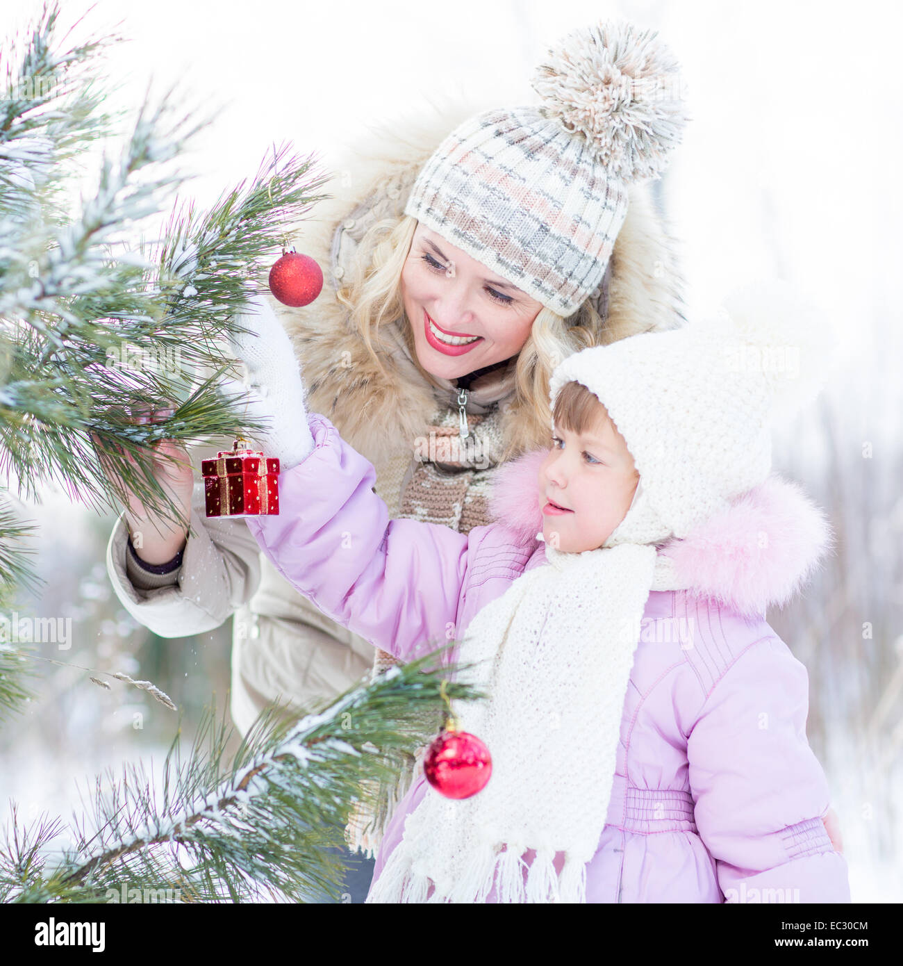 Happy mother and child decorating christmas tree outdoor wintertime - Stock Image