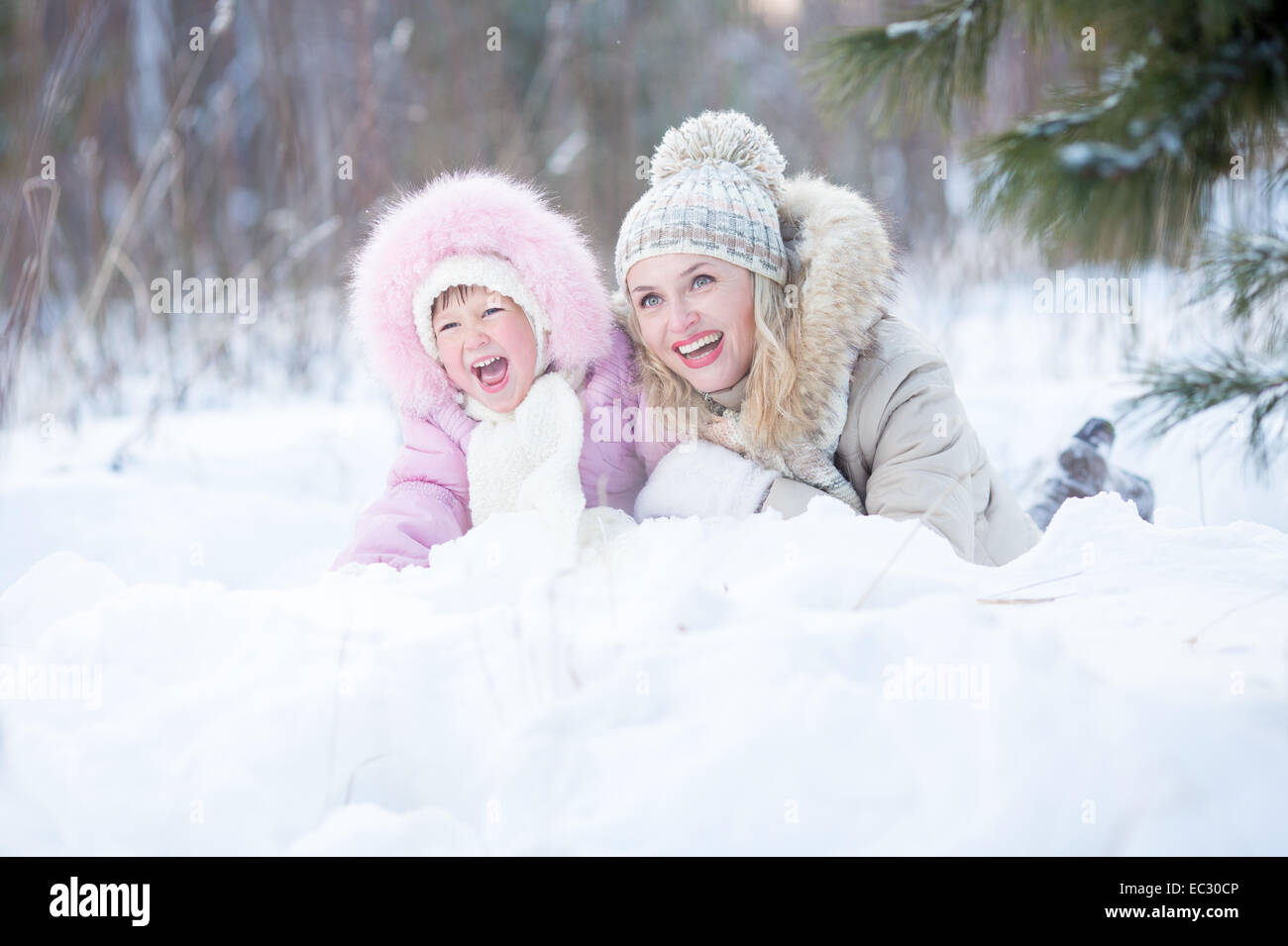 Happy mother and kid lying in snow outdoor - Stock Image