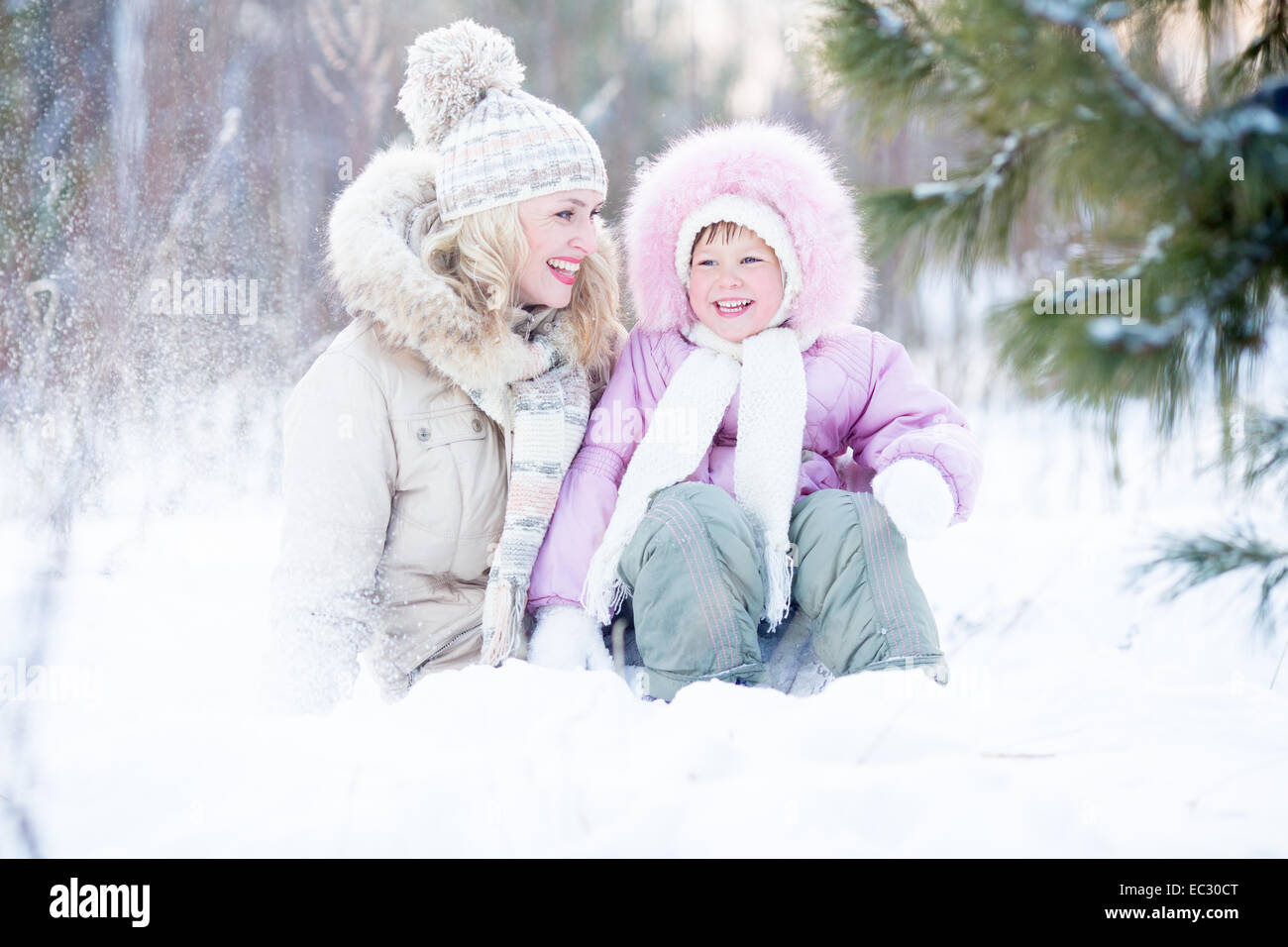 Happy family sitting in snow outdoor wintertime - Stock Image