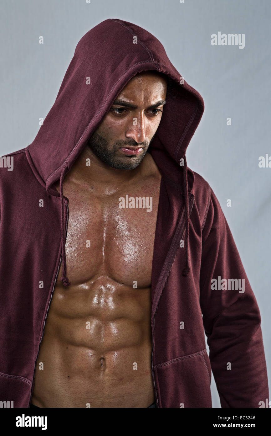 young male wearing open hoody showing muscular chest - Stock Image