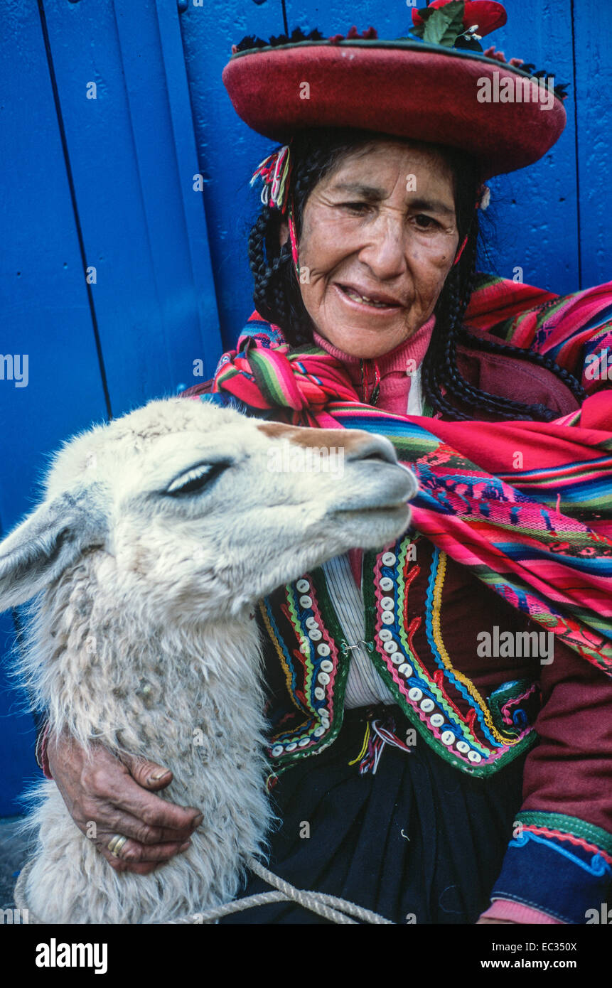 Women dressed in traditional costume poses with a llama