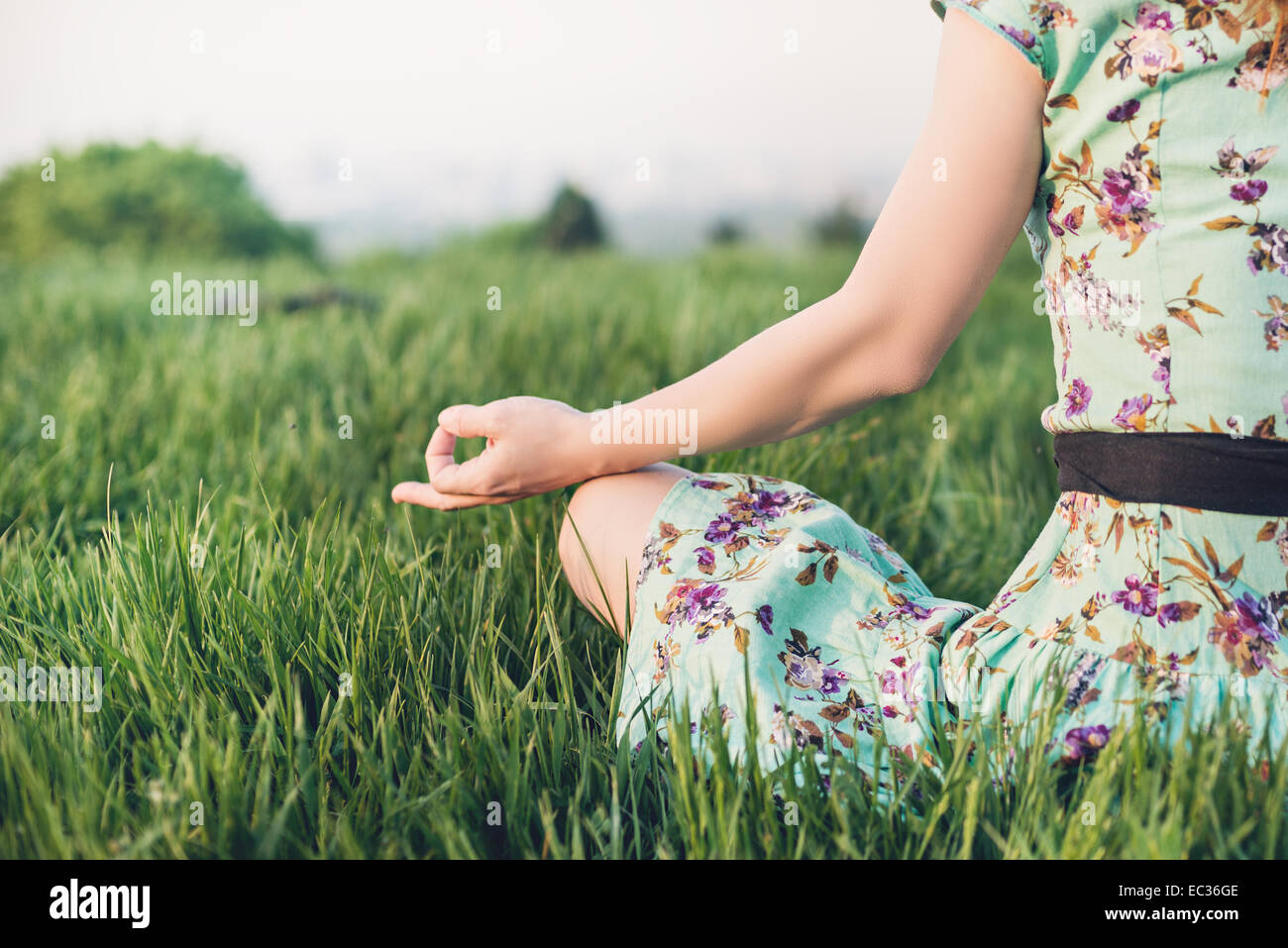 Pretty woman meditate in the park - Stock Image