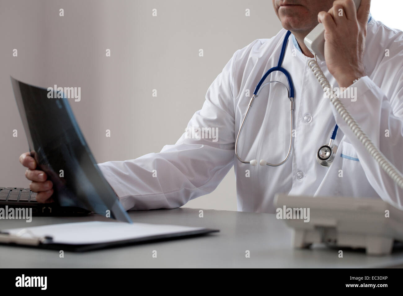 Senior doctor is talking on the phone in his consulting room viewing a x-ray image. - Stock Image