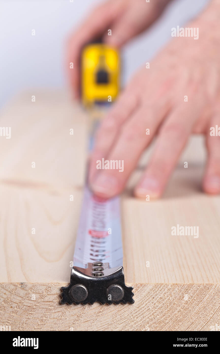 Man measures a wooden plank  by tape measure. - Stock Image