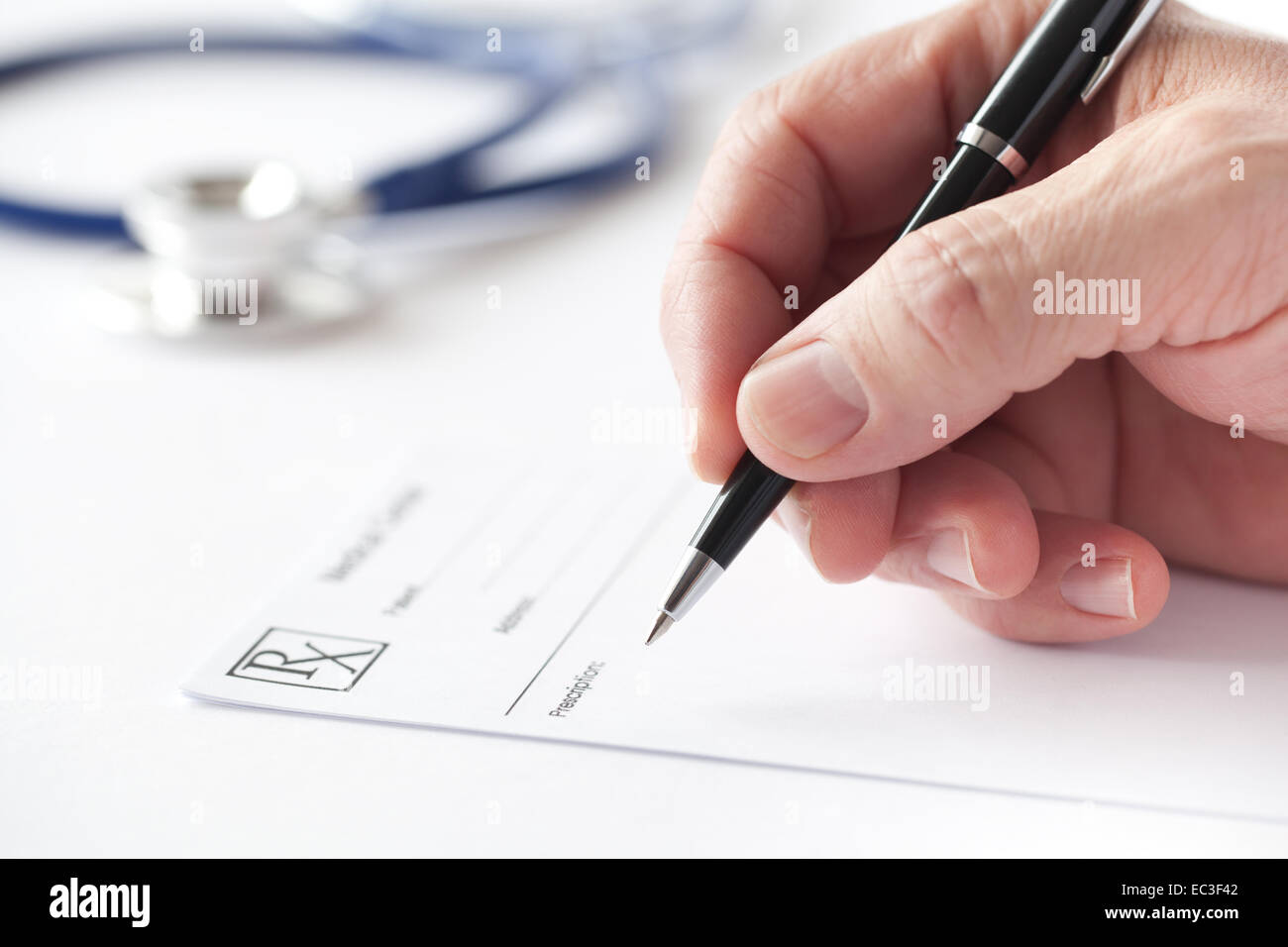 Doctor is writing a prescription in the consulting room. - Stock Image