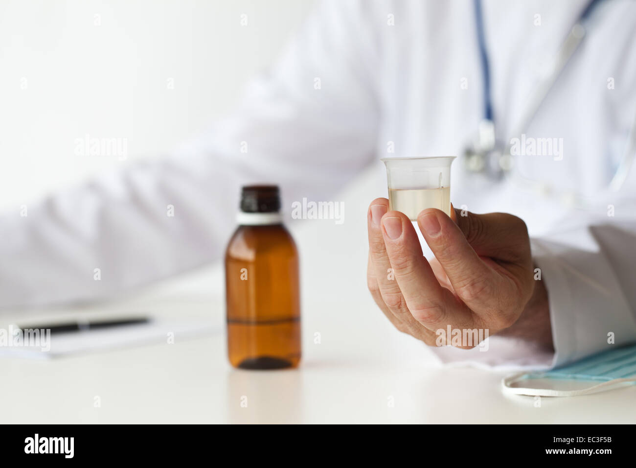 Doctor is giving a medicine in the consulting room. - Stock Image