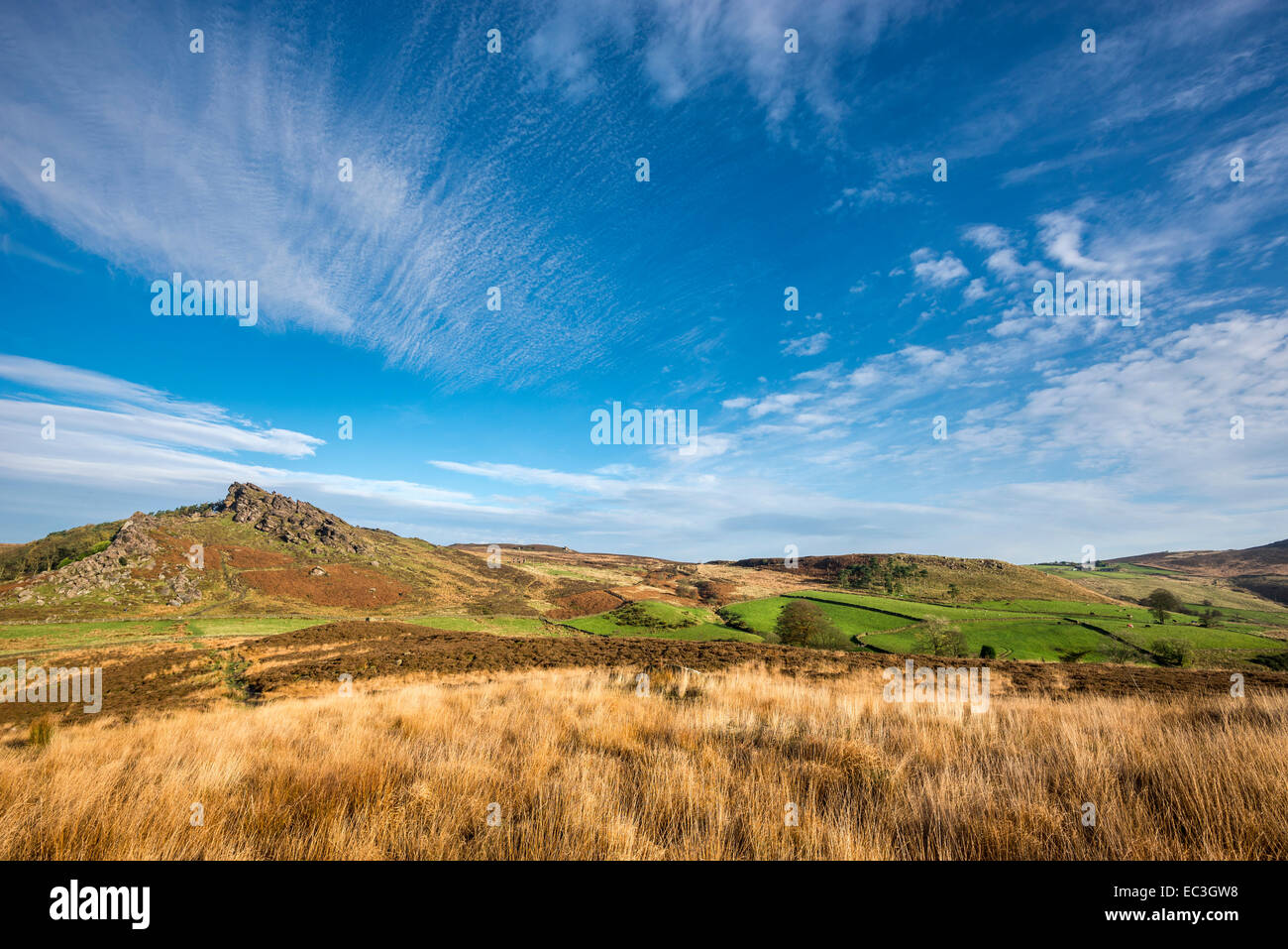 Blue sky with patterns of high clouds above a moorland landscape of heather and grasses with gritstone outcrops - Stock Image