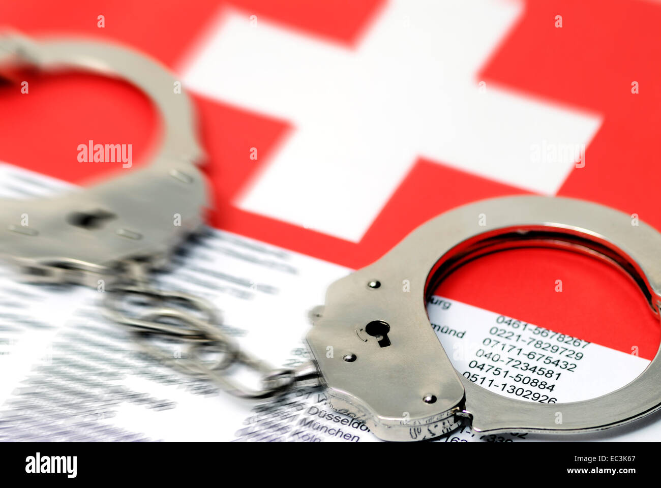 Handcuffs, address list and Swiss flag, illegal earnings - Stock Image