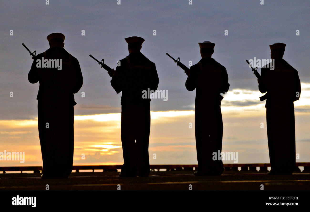 US Navy sailors from the amphibious assault ship USS Bataan are silhouetted by the setting sun during a burial at - Stock Image