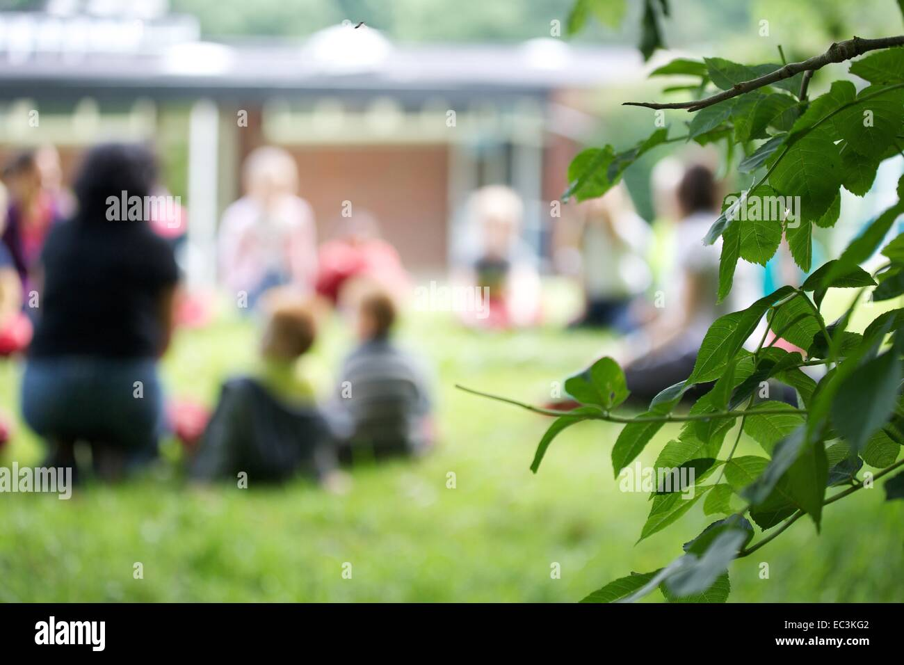 A group of british schoolchildren having a lesson outside on the grass with their teacher - Stock Image