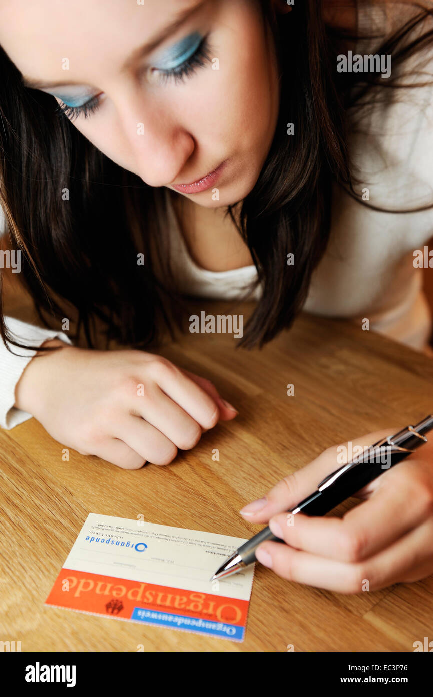 Young woman with organ donation card - Stock Image