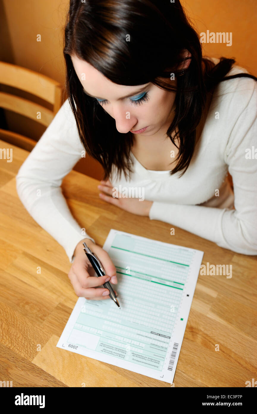 young woman filling out tax form stock photo: 76300666 - alamy