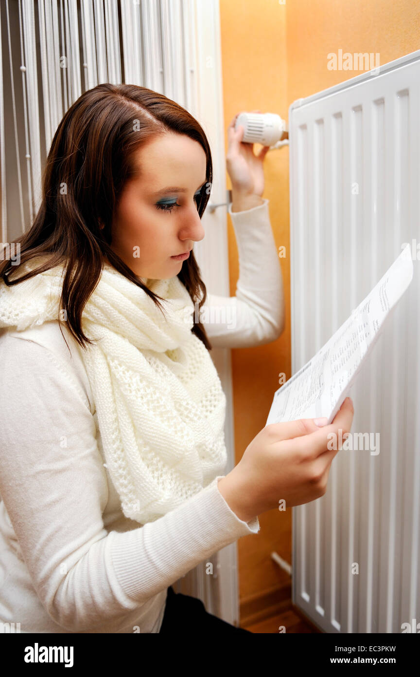 Young woman with heat billing in front of a heater, heating costs - Stock Image