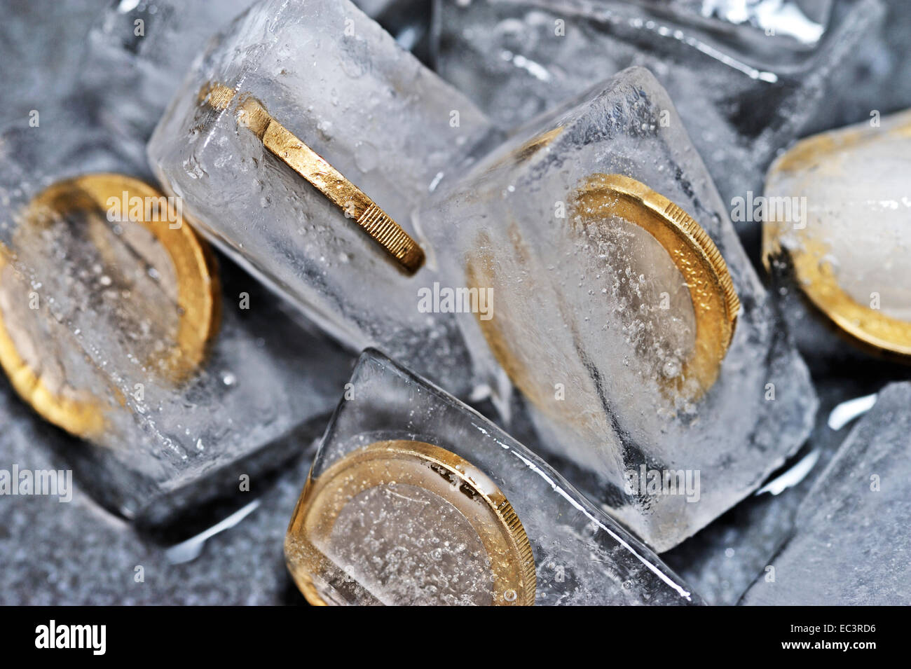 One euro coins in ice cubes, symbolic picture for frozen account - Stock Image