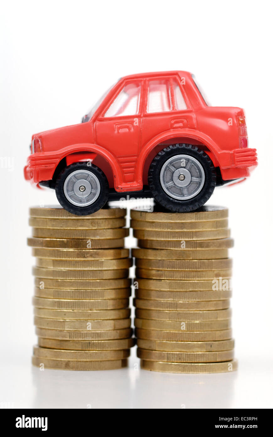Toy car and euro coins, road charge and motor vehicle tax - Stock Image