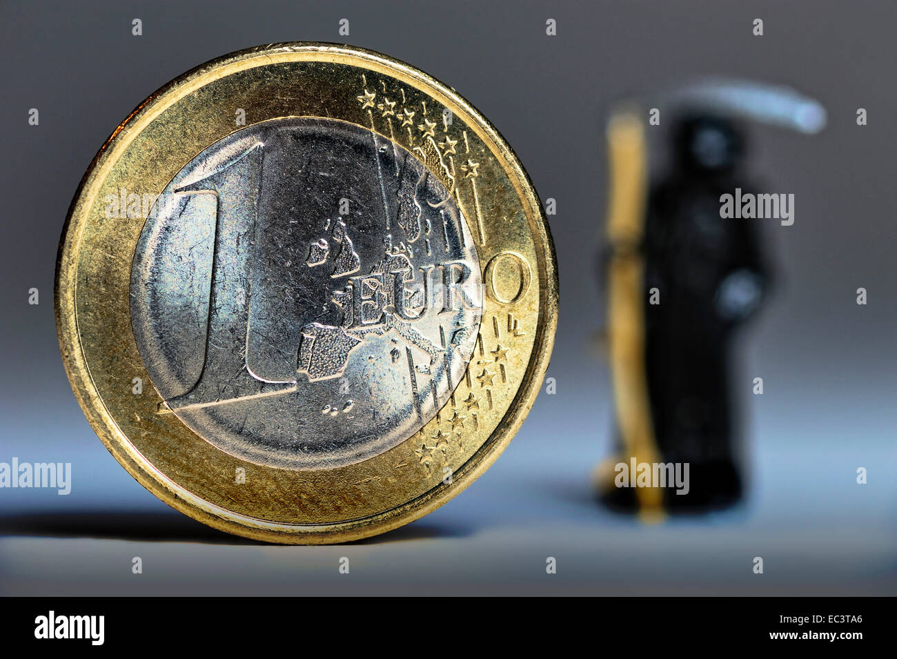 The Grim Reaper next to an euro coin, European debt crisis - Stock Image