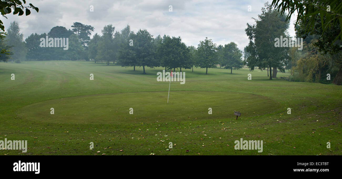 Bonfire smoke drifts over golf green and fairway - Stock Image