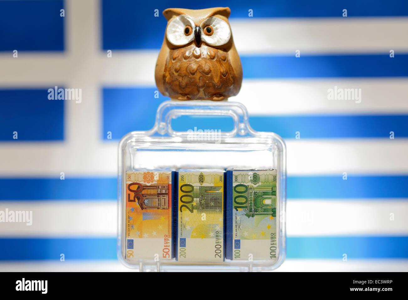 Greek owl sitting on money suitcase, EU aid for Greece - Stock Image