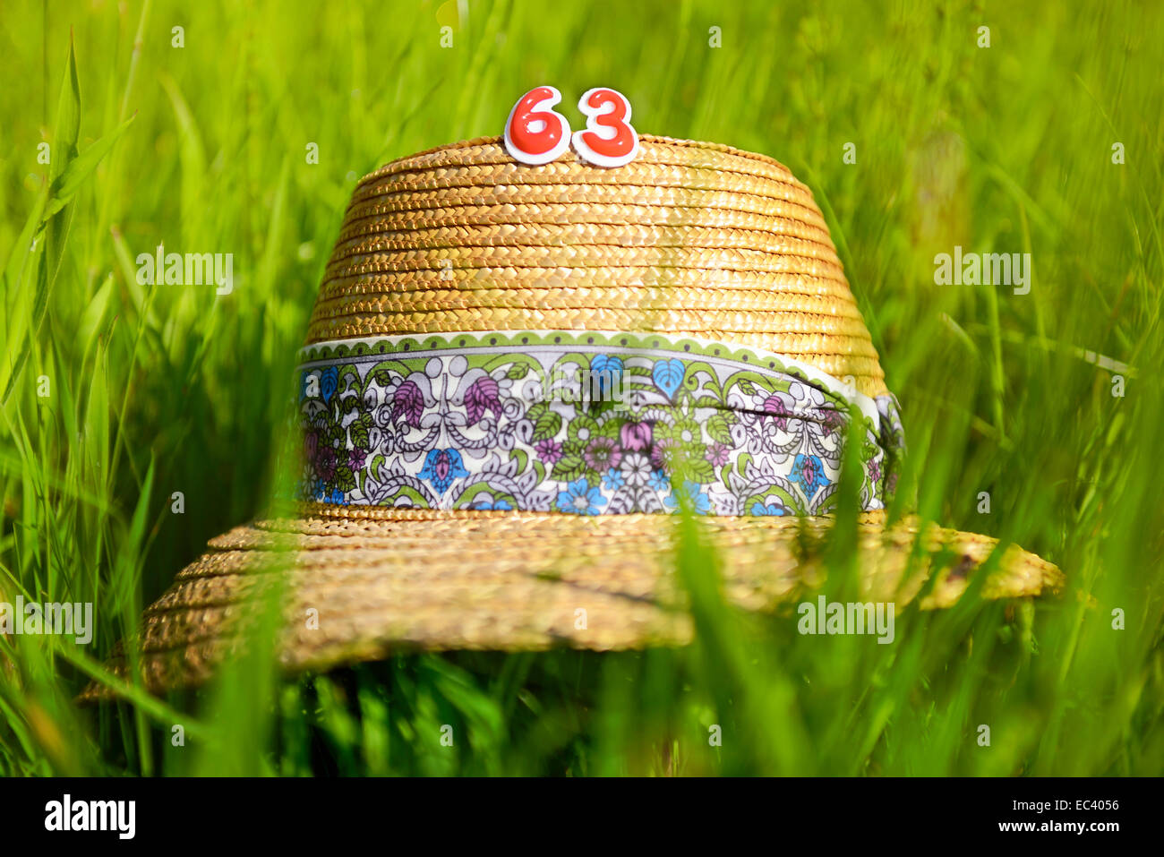 Sun hat and number 63, pension at age 63 - Stock Image