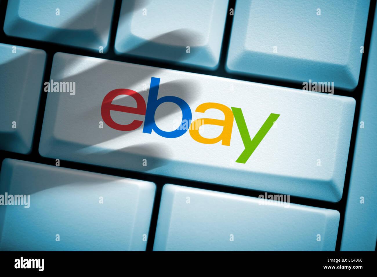 Computer key, ebay logo and black hand, hacked accounts - Stock Image