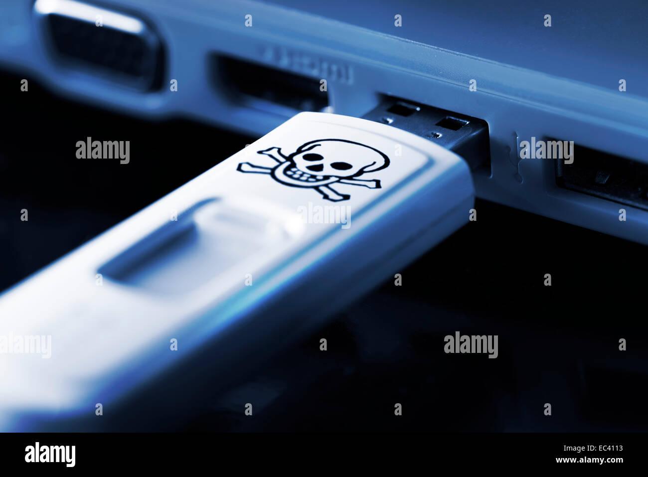 Skull sign on USB flash drive, computer virus - Stock Image