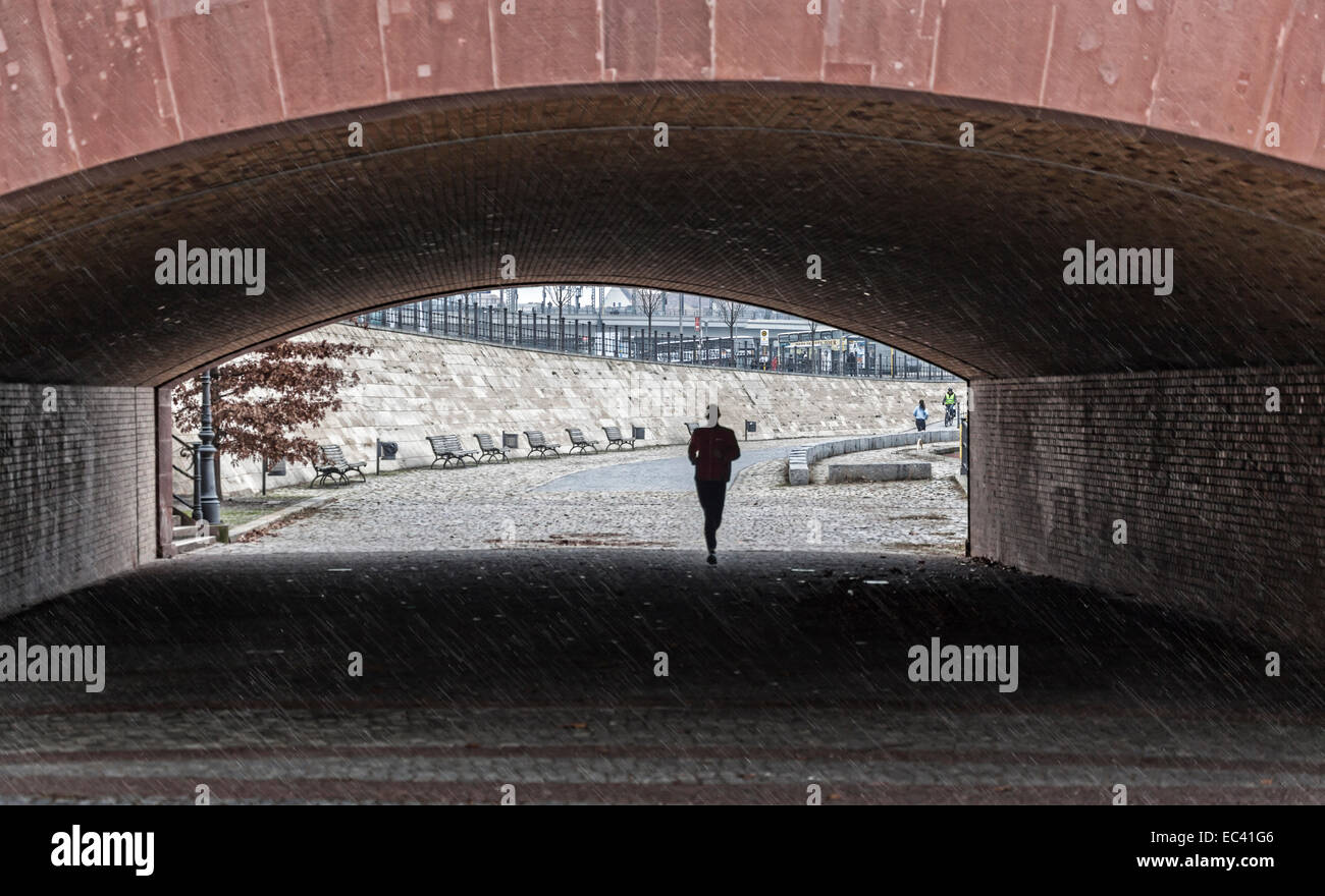 Jogging in the rain below the Moltke bridge in Berlin - Stock Image