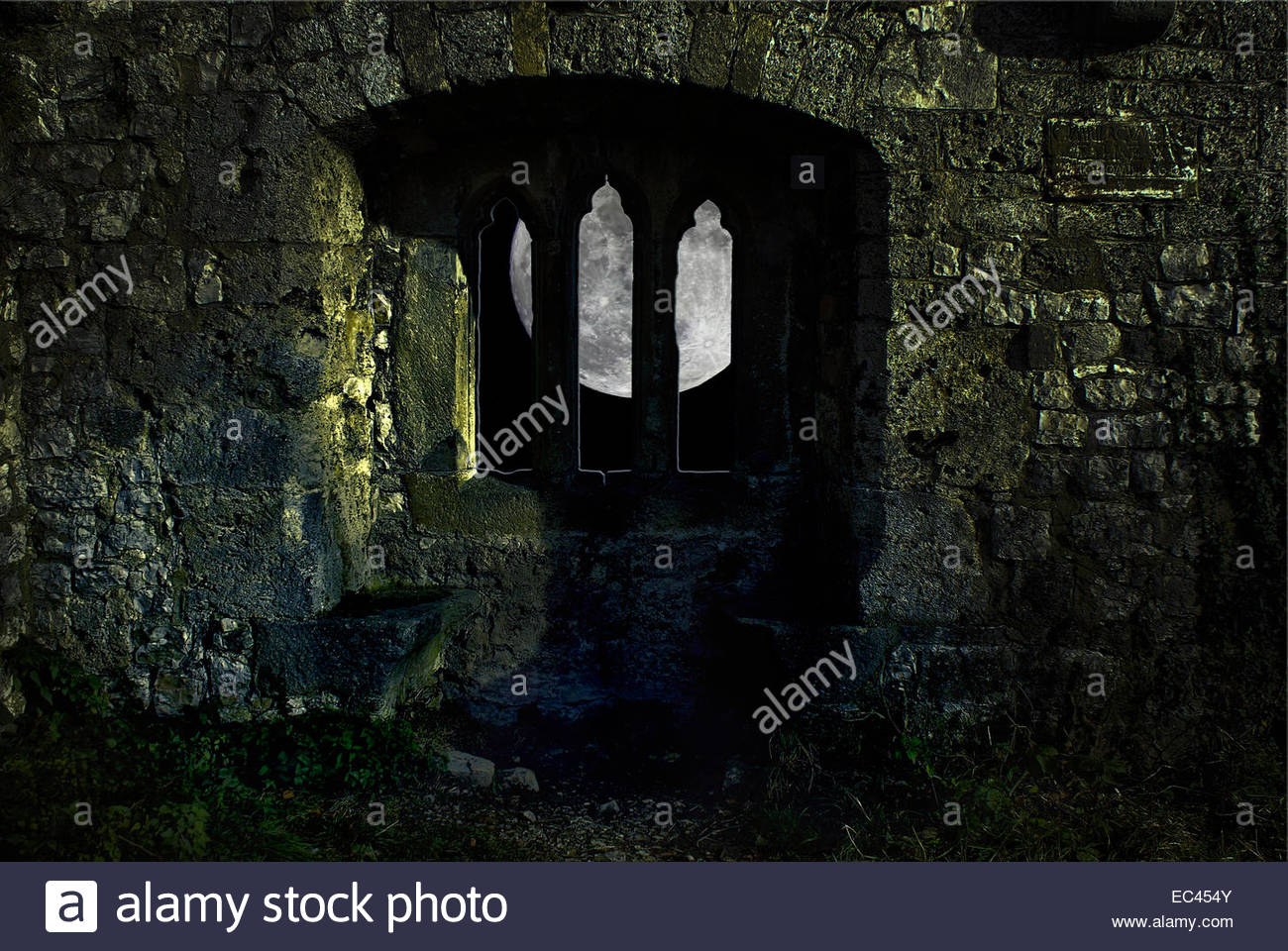 Big fat moon shines through medieval castle window photo, composition. Stock Photo