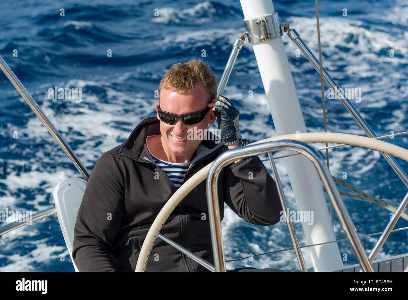 Cheerful skipper on the helm of sailing boat - Stock Image