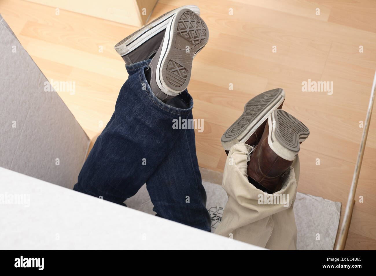 Feet Protruding from a moving box - Stock Image