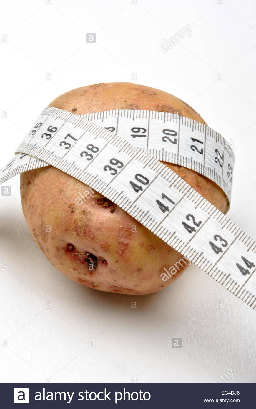 fresh organic potato and centimeter tape measure - Stock Image