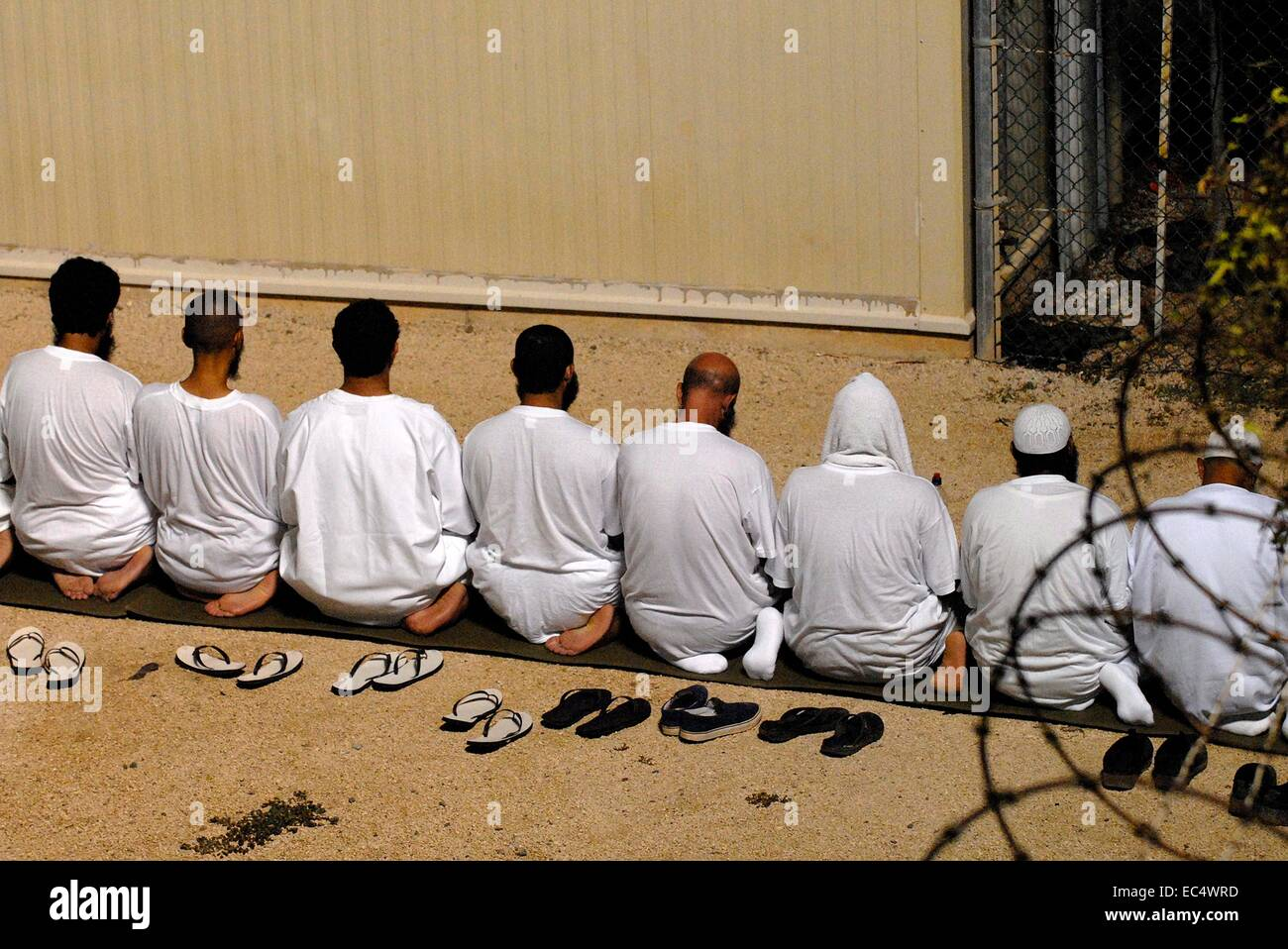 Enemy combatants held as detainees at the Joint Task Force Guantanamo observe morning prayer before sunrise inside - Stock Image
