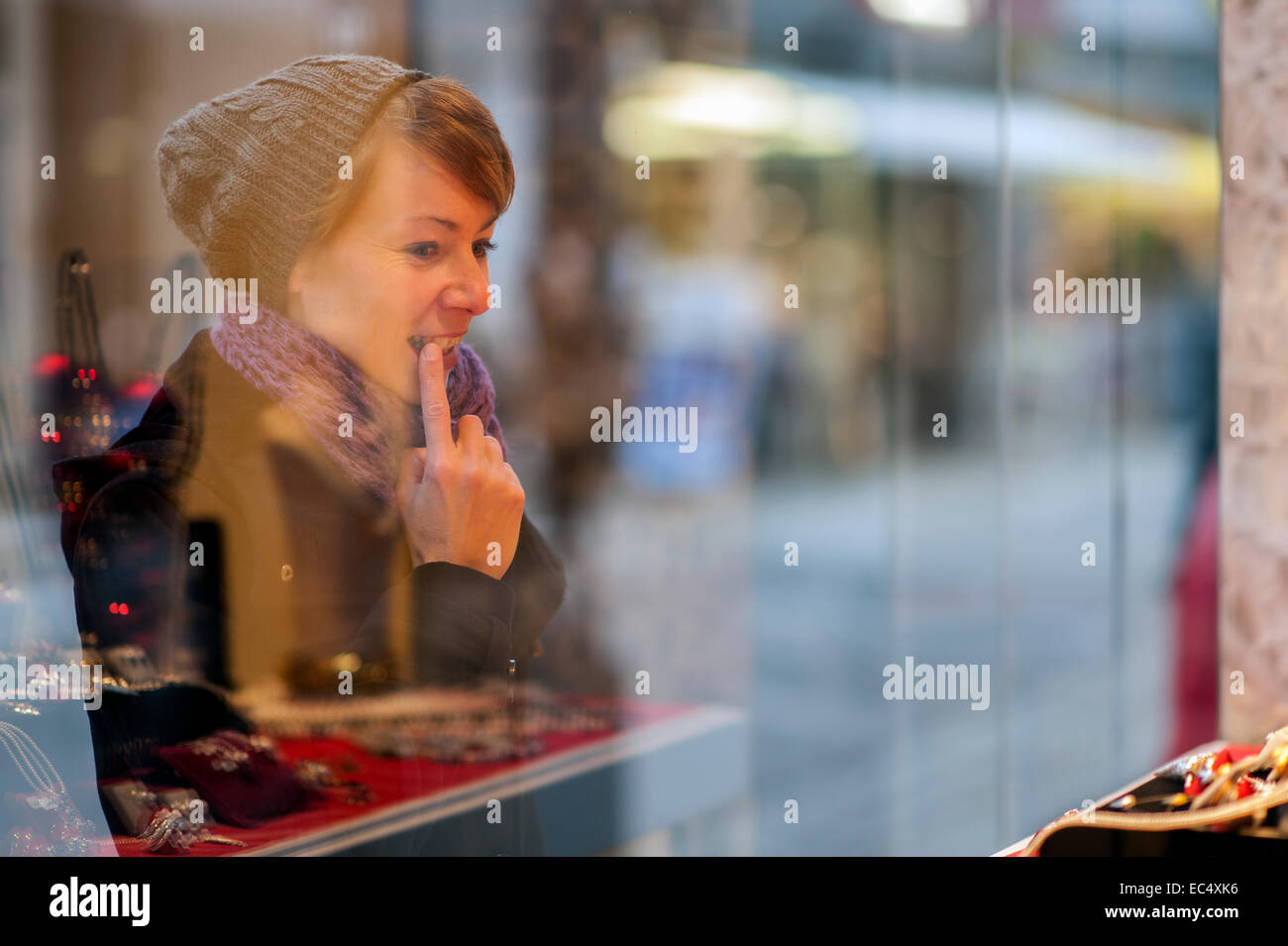young woman considered the window of a jeweller s - Stock Image