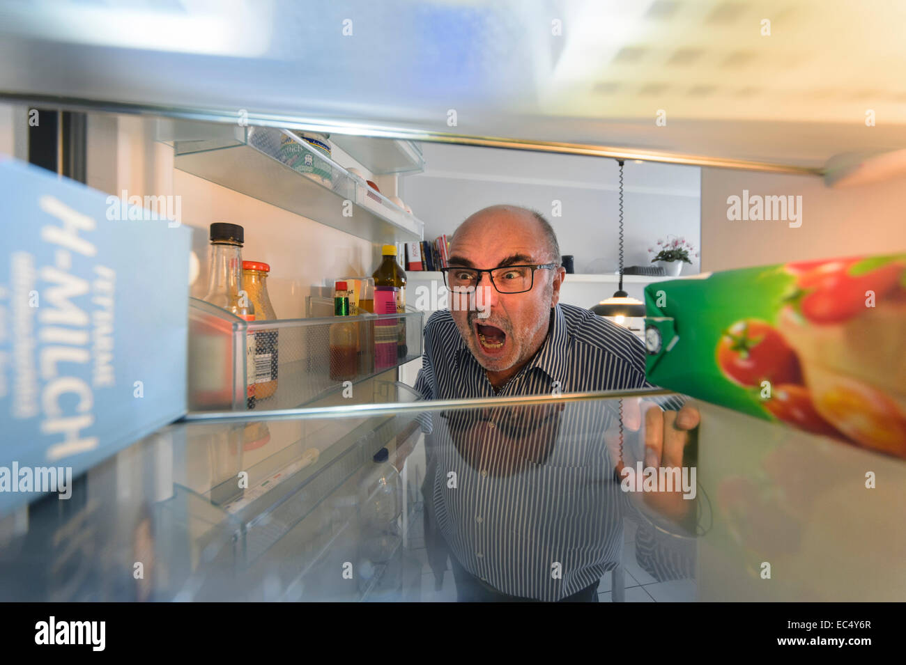 a senior looking in search of beer in the fridge angry - Stock Image