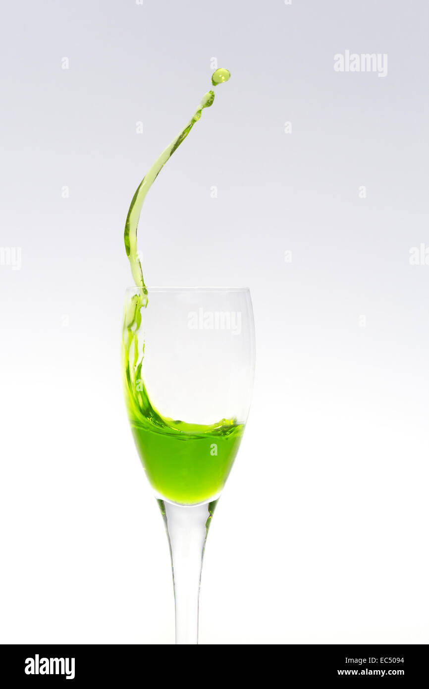 Upper part of a champagne flute with splashing liquid - Stock Image