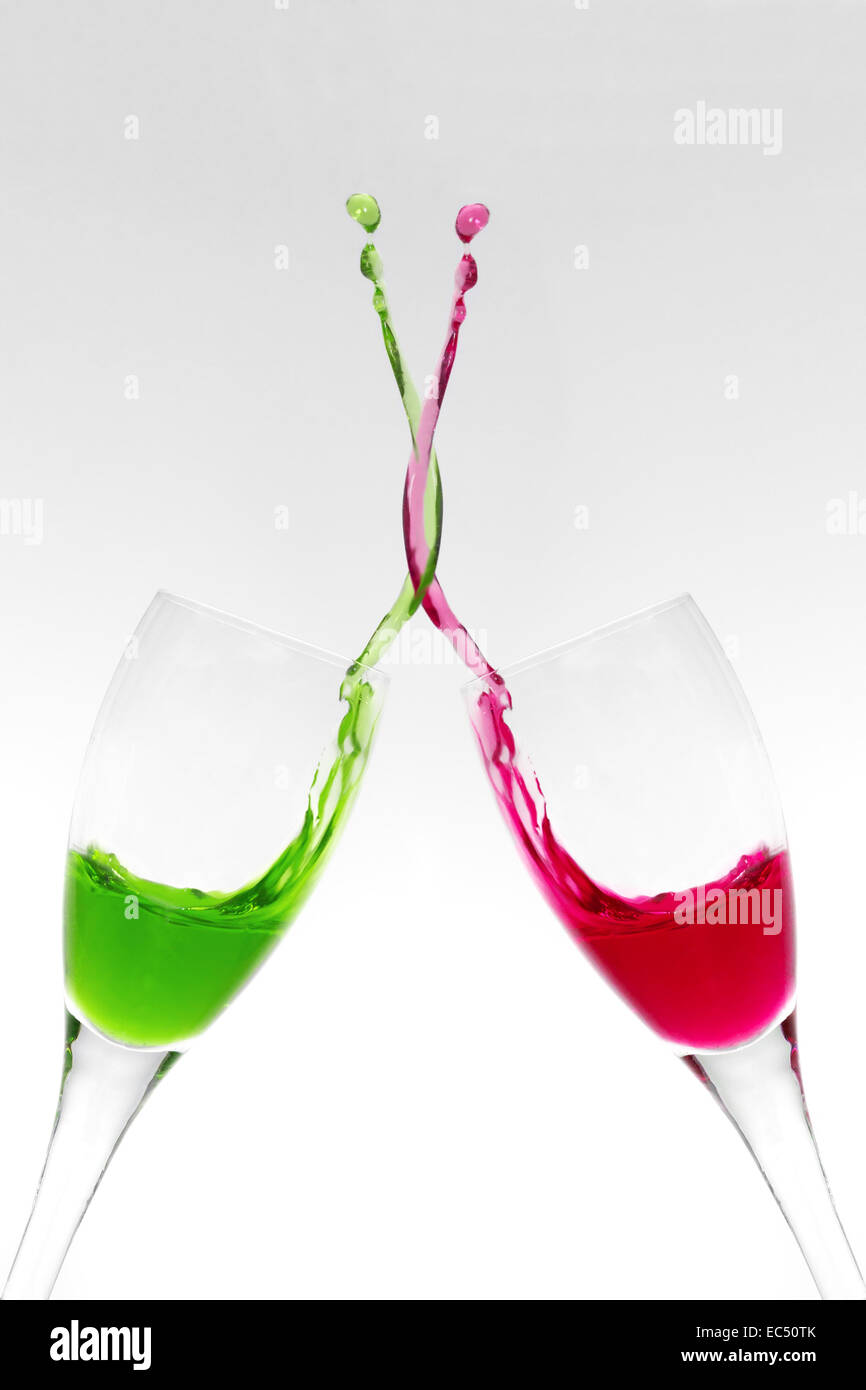Two champagne glasses clinking and mixing liquids - Stock Image