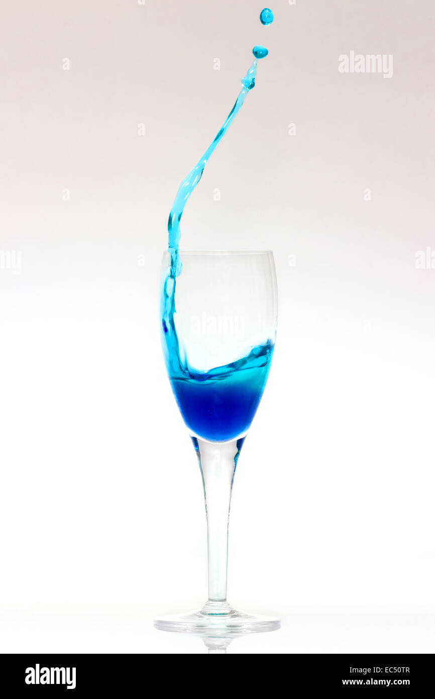 Blue liquid splashes out of a glass - Stock Image