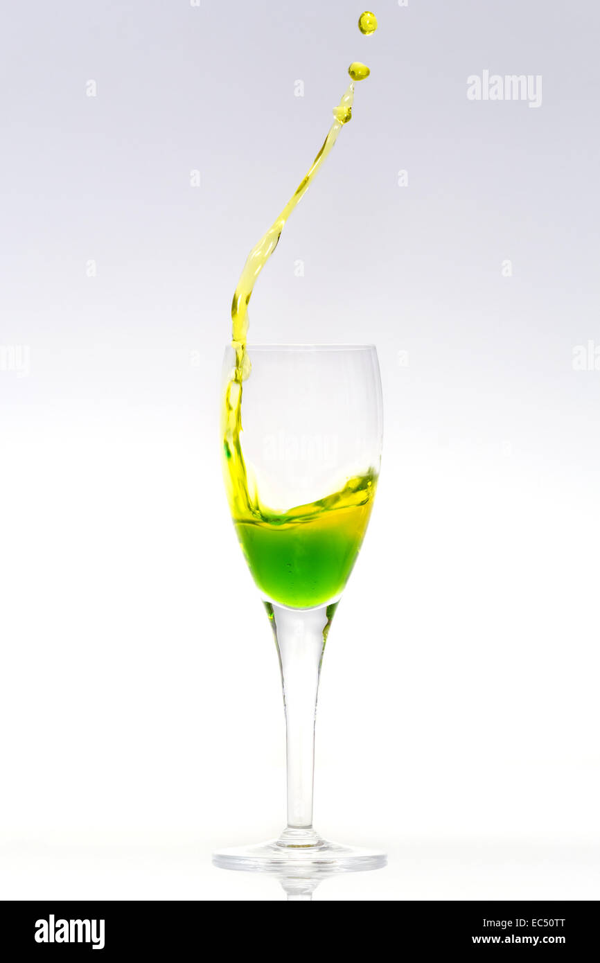 Green and yellow liquid is splashing out of a glass - Stock Image