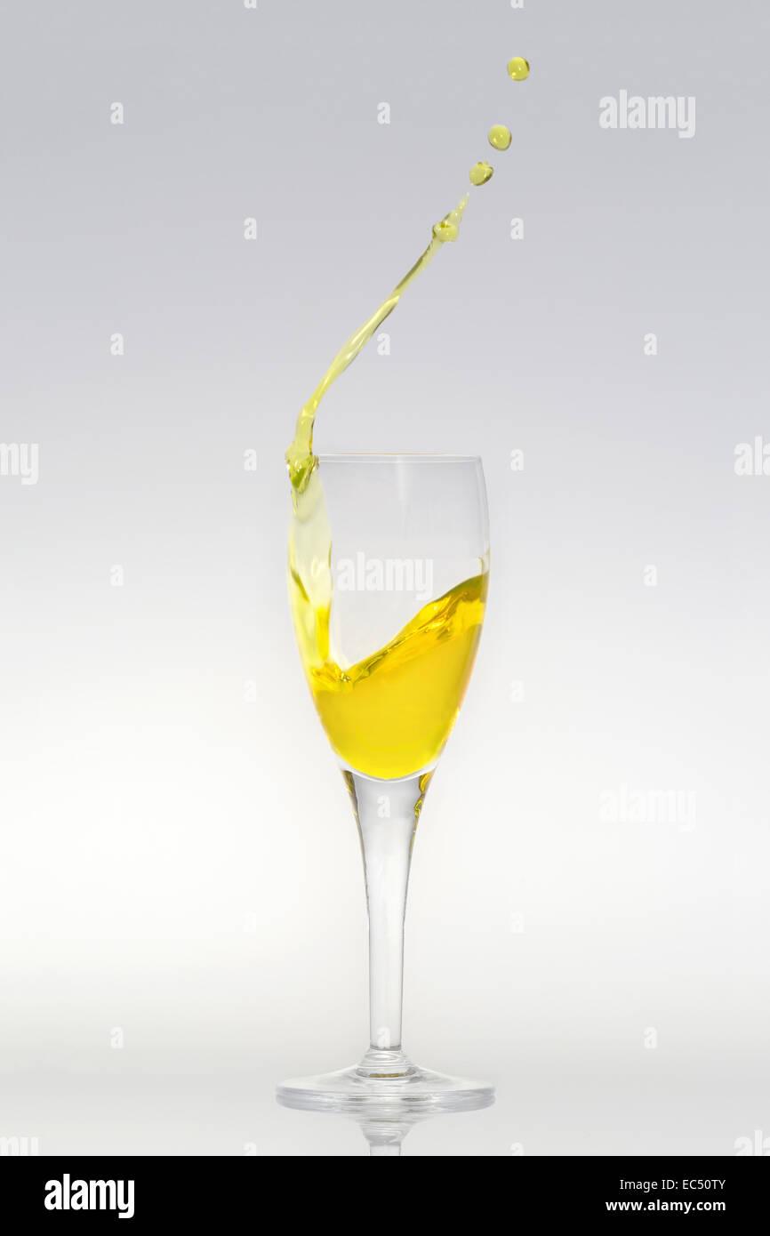 Champagne flute with splashing liquid - Stock Image