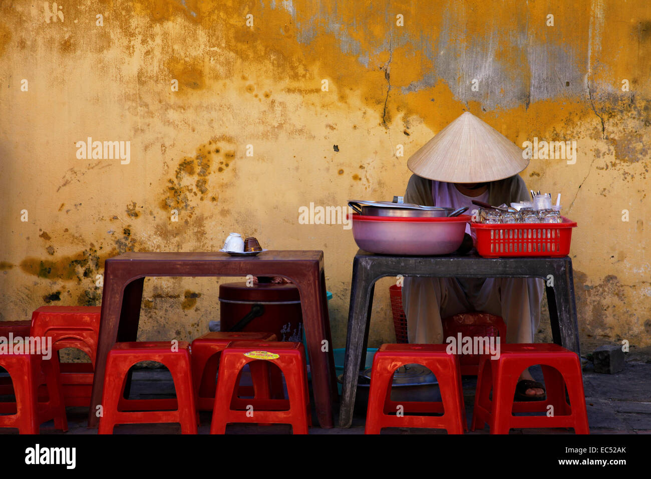 A asien woman waits Viet Nam on for customers in its road conditions, Hoi - Stock Image
