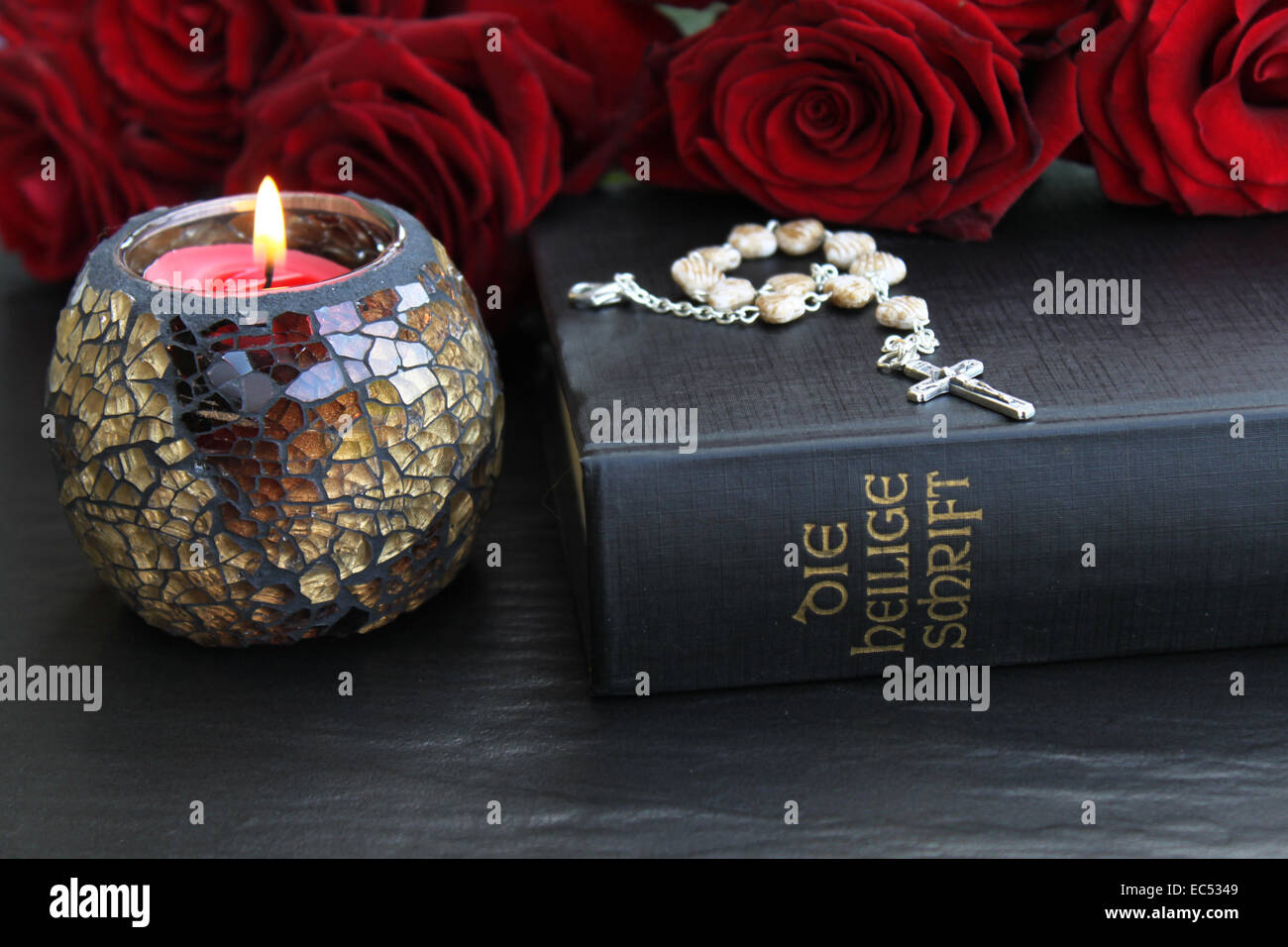 The Holy Scriptures with candle and rosary - Stock Image