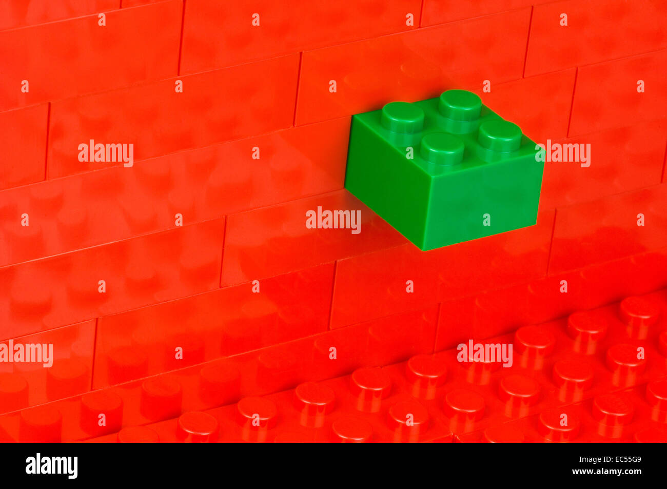 Green building block in a wall of red one - Stock Image