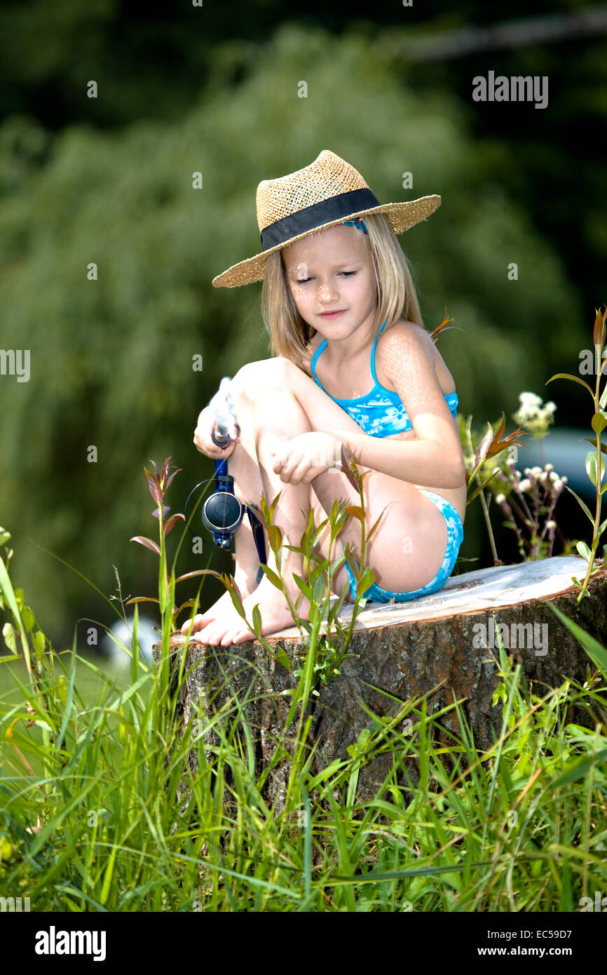 young fishing girl sitting on a stub at the lake - Stock Image