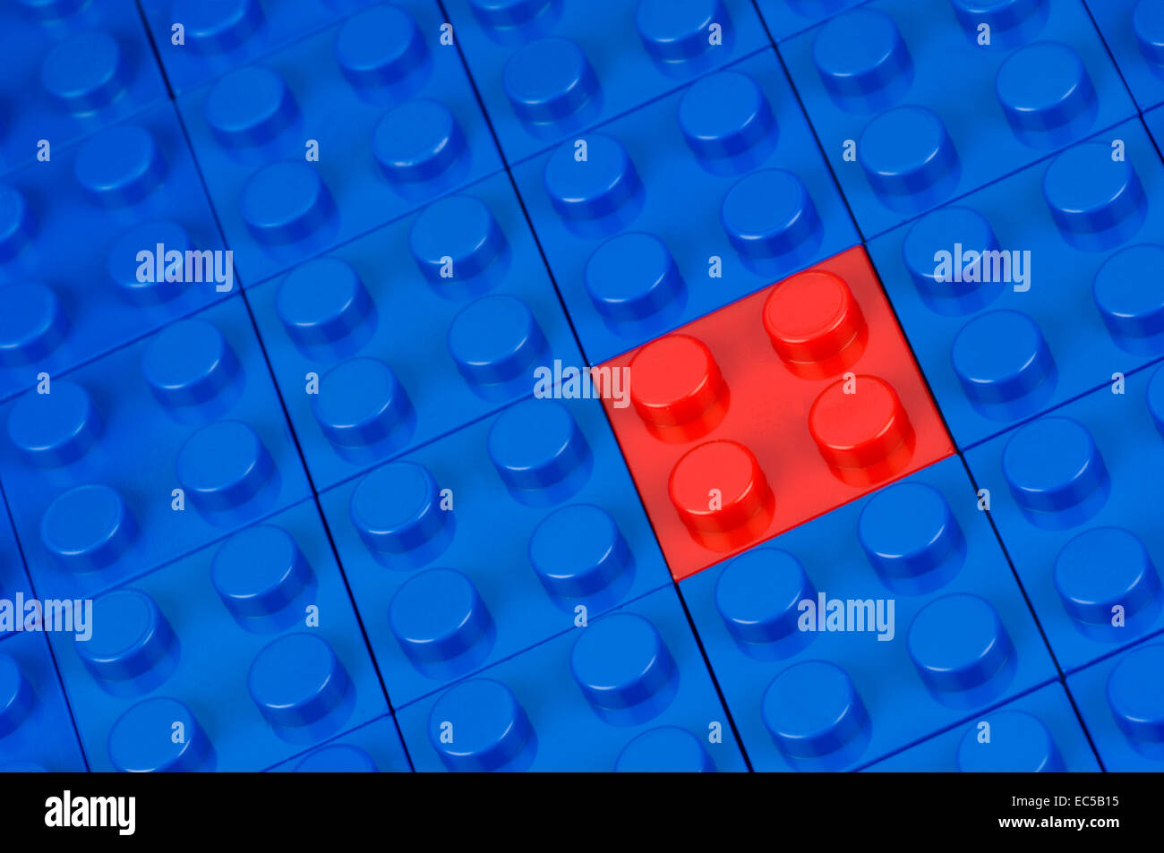 Red building block in a field of blue ones - Stock Image