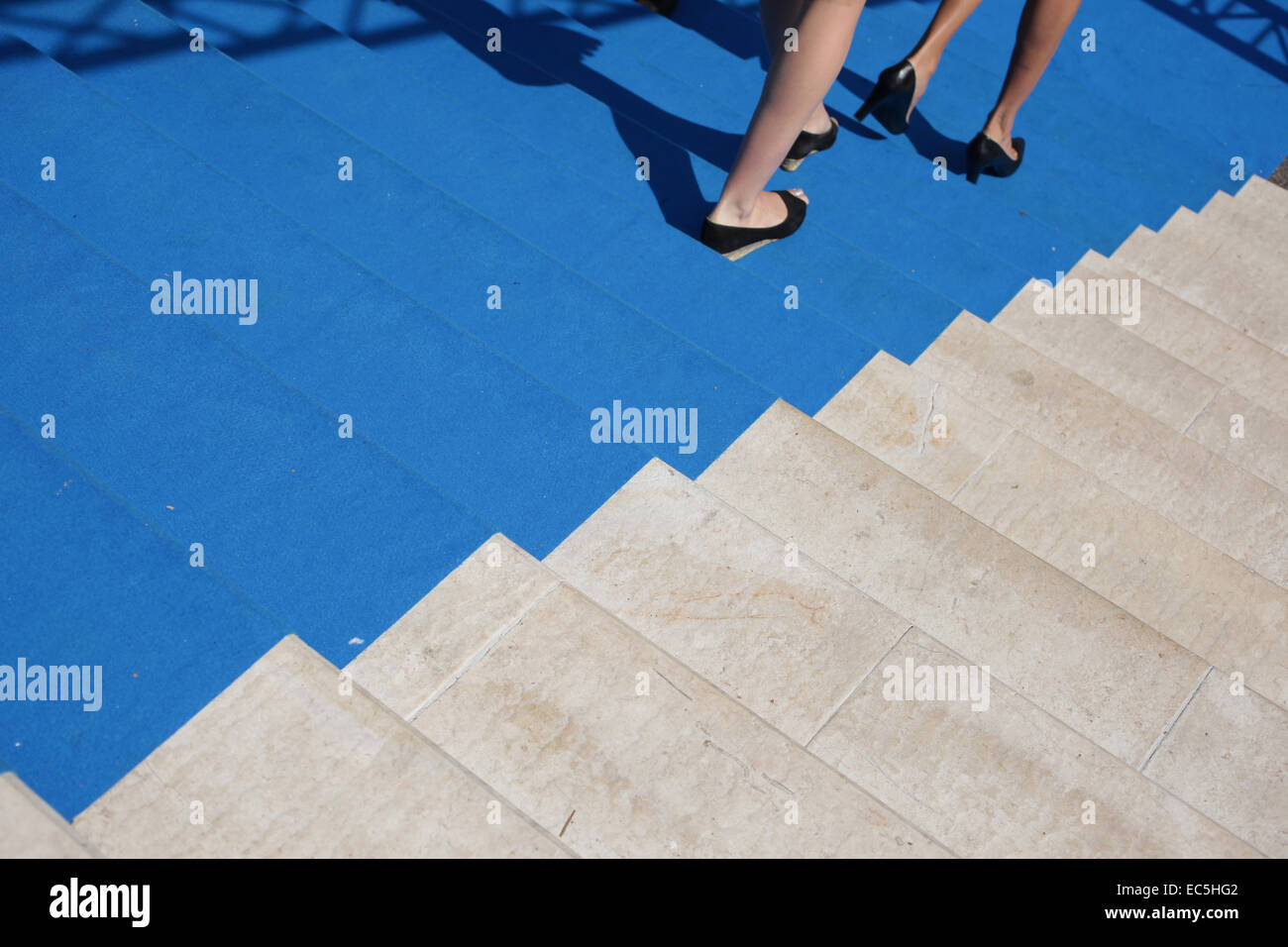 nice girls legs on stairs covered whith a blue carpet - Stock Image