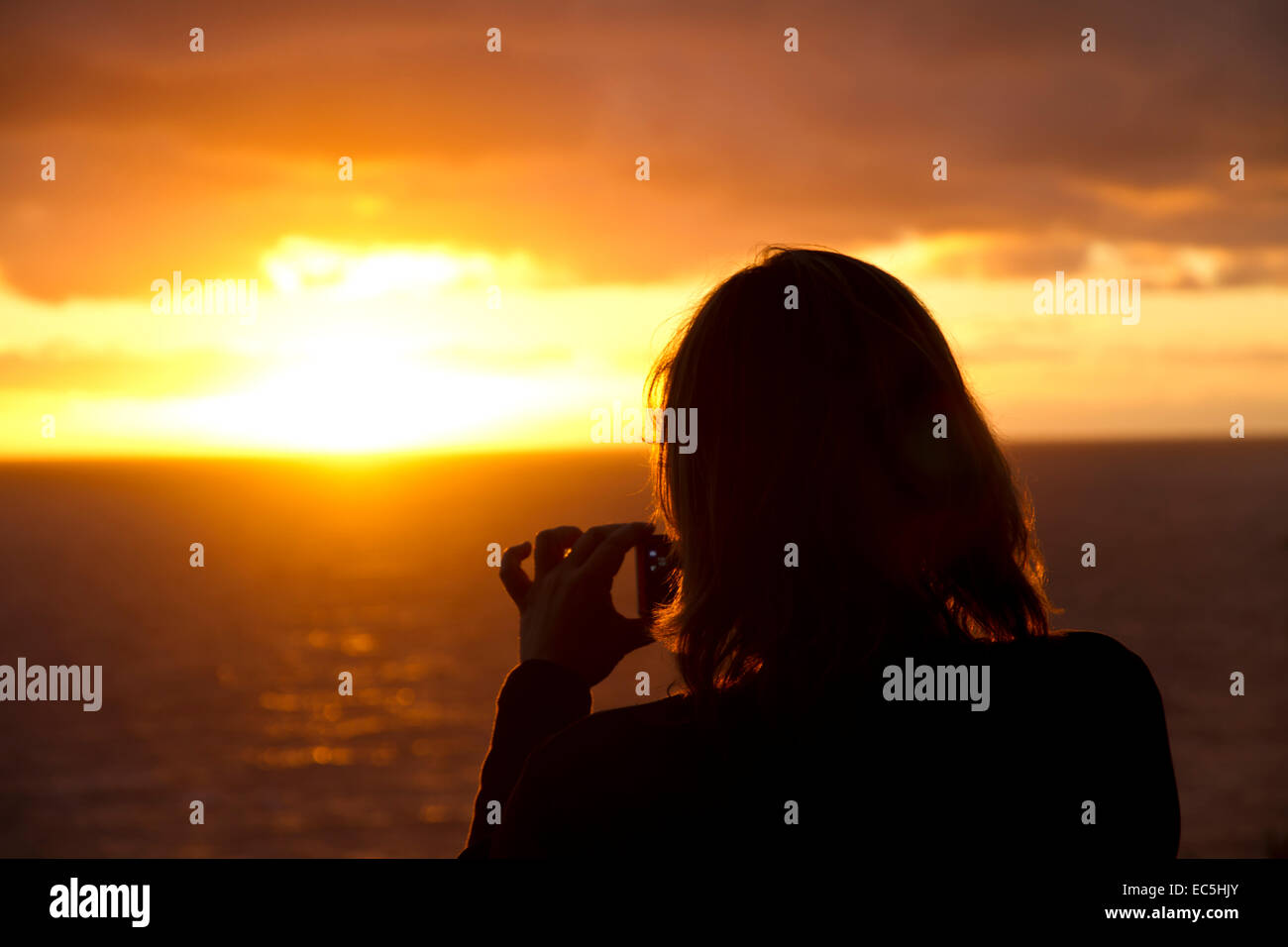 Woman photographed sunset at sea - Stock Image